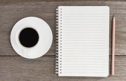 Notizbuch mit Kaffeetasse auf hölzernem Hintergrund Stockfotografie