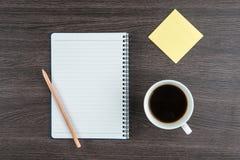 Notizbuch mit klebender Anmerkung und Tasse Kaffee des Bleistifts Lizenzfreies Stockfoto