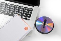 Notizbuch mit leerer CD zum Computer auf Weiß. Stockfoto