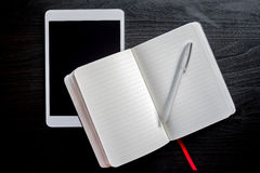 Notizbuch mit rotem Bookmark auf einer dunklen Tabelle mit einem Stift und einem weißen Tablet-Computer Lizenzfreie Stockfotos