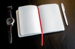 Notizbuch mit rotem Bookmark auf einer dunklen Tabelle mit einem Stift und einer Uhr Lizenzfreie Stockbilder