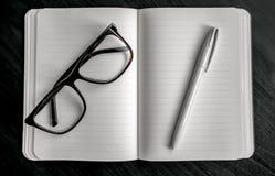 Notizbuch mit rotem Bookmark auf einer dunklen Tabelle mit einem Stift und Gläsern Lizenzfreie Stockfotografie