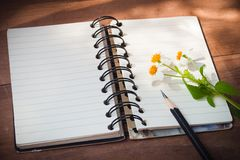 Notizbuch mit schwarzem Bleistift, weiße Blumen auf Holztisch Stockfotografie