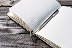 Notizbuch mit Stift auf altem Holztisch Lizenzfreies Stockfoto