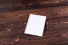Notizbuch mit Stift auf brauner Tabelle stockbilder