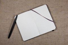 Notizbuch mit Stift auf Leinwand Lizenzfreie Stockfotos
