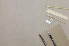 Notizbuch mit Stift- und Bleistiftradiergummi auf Hintergrund des braunen Papiers Stockfotografie