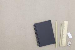 Notizbuch mit Stift- und Bleistiftradiergummi auf Hintergrund des braunen Papiers Stockbild