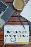 Notizbuch mit Text innerhalb des Internet-Marketings auf Tabelle mit coffe Stockfotos