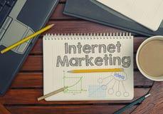 Notizbuch mit Text innerhalb des Internet-Marketings auf Tabelle mit coffe Stockfotografie