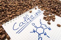 Notizbuch mit Texttitelkoffein und gemalter chemischer Formel des Koffeins wird durch gebratene gebrauchsfertige Körner des Kaffe lizenzfreie stockfotografie