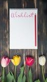 Notizbuch mit Wunschlistewort auf hölzernem Hintergrund mit Frühling blüht Tulpen Frau ` s Wunschlistekonzept Abschluss oben Lizenzfreies Stockbild