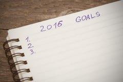Notizbuch mit Zielen von Jahr 2016 auf hölzernem Hintergrund Lizenzfreie Stockfotografie