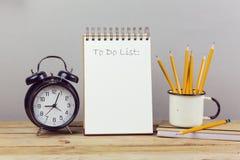 Notizbuch mit, zum der Liste, der Bleistifte und des Weckers zu tun Stockfoto