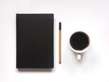 Notizbuch oder Buch mit Stift und heißer schwarzer Kaffee auf weißem Schreibtisch Beschneidungspfad eingeschlossen Flache Lage Lizenzfreie Stockbilder