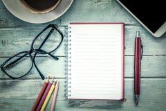 Notizbuch, Stift, Mobiltelefon, Gläser, Bleistiftfarbe und Kaffee Lizenzfreie Stockfotos