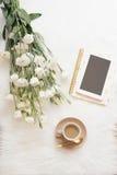 Notizbuch, Tablette, ein Tasse Kaffee und weiße Blumen eines großen Blumenstraußes auf dem Boden auf einem weißen Pelzteppich Fre lizenzfreie stockfotografie