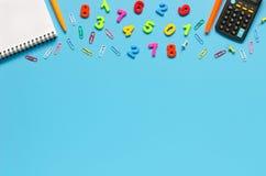 Notizbuch, Taschenrechner, Stift, bunte Zahlen auf blauem Hintergrund Lizenzfreies Stockfoto