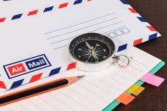 Notizbuch, Umschläge schicken, Notizbuch, Kompass per Luftpost und Bleistift flehen an an stockfotografie