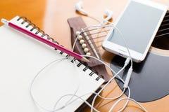 Notizbuch und Bleistift auf der Gitarre, Musik schreibend Lizenzfreies Stockfoto