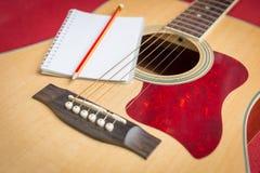 Notizbuch und Bleistift auf Gitarre Lizenzfreie Stockfotos