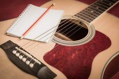 Notizbuch und Bleistift auf Gitarre Lizenzfreies Stockfoto