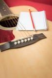 Notizbuch und Bleistift auf Gitarre Lizenzfreie Stockbilder
