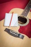 Notizbuch und Bleistift auf Gitarre Lizenzfreies Stockbild