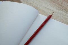 Notizbuch und Bleistift auf hölzerner Tabelle Stockfoto