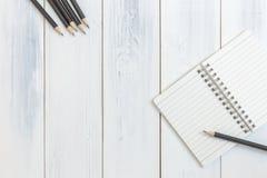 Notizbuch und Bleistift auf Holztisch, Draufsicht, Konzept des Arbeitsplatzes, Büroartikel, Hintergrund Lizenzfreies Stockbild