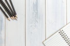 Notizbuch und Bleistift auf Holztisch, Draufsicht, Konzept des Arbeitsplatzes, Büroartikel, Hintergrund Stockfoto