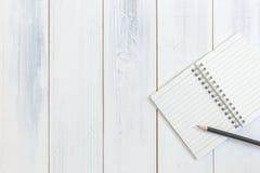 Notizbuch und Bleistift auf Holztisch, Draufsicht, Konzept des Arbeitsplatzes, Büroartikel, Hintergrund Lizenzfreie Stockfotos
