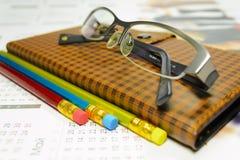 Notizbuch und Bleistift mit Gläsern lizenzfreies stockfoto