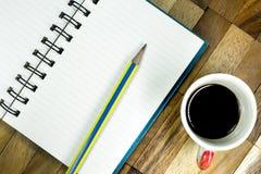 Notizbuch und Bleistift mit schwarzem Kaffee auf Tabelle stockfotografie