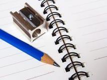 Notizbuch und Farbbleistiftbriefpapier auf Weiß Stockfotografie