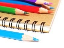 Notizbuch und Farbbleistiftbriefpapier lokalisiert auf Weiß Lizenzfreie Stockfotografie