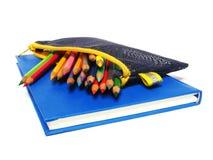 Notizbuch und Farbbleistiftbriefpapier lokalisiert auf Weiß Lizenzfreie Stockfotos