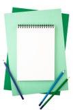 Notizbuch und farbige Bleistifte auf Blättern des strukturierten Papiers Stockbilder