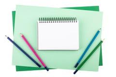 Notizbuch und farbige Bleistifte auf Blättern des strukturierten Papiers Stockbild