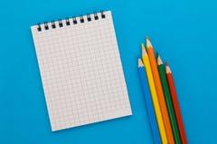 Notizbuch und farbige Bleistifte auf einem blauen Hintergrund Lizenzfreies Stockfoto