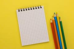 Notizbuch und farbige Bleistifte auf einem gelben Hintergrund Stockfotos