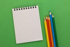Notizbuch und farbige Bleistifte auf einem grünen Hintergrund Stockfotografie