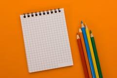 Notizbuch und farbige Bleistifte auf einem orange Hintergrund Stockbild