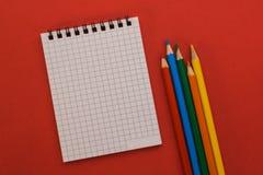 Notizbuch und farbige Bleistifte auf einem roten Hintergrund Lizenzfreies Stockfoto