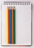 Notizbuch und farbige Bleistifte auf einem weißen Hintergrund Stockbild
