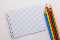 Notizbuch und farbige Bleistifte auf einem weißen Hintergrund Stockbilder