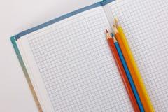 Notizbuch und farbige Bleistifte auf einem weißen Hintergrund Lizenzfreie Stockfotografie