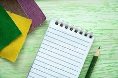 Notizbuch und farbiges Gewebe Lizenzfreies Stockfoto