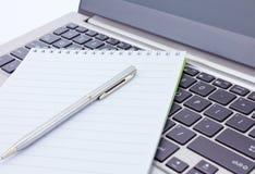 Notizbuch- und Federlüge auf der Tastatur Stockfoto