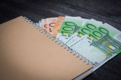 Notizbuch und Geld auf dem Tisch Notizblock- und Eurobanknoten auf dunklem hölzernem Hintergrund lizenzfreies stockfoto